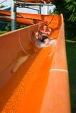 Equitação do homem abaixo de uma corrediça de água Fotografia de Stock