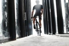 Equitação do homem da bicicleta do esporte dentro do túnel de vidro urbano com luz fotos de stock royalty free
