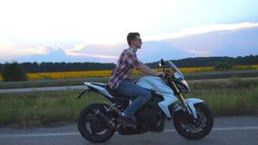 Equitação do homem novo em um velomotor moderno do esporte Motociclista considerável em uma camisa e nos vidros que conduzem sua  filme
