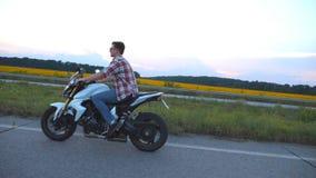 Equitação do homem novo em um velomotor moderno do esporte Motociclista considerável em uma camisa e nos vidros que conduzem sua  vídeos de arquivo