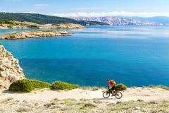Equitação do motociclista da montanha na bicicleta em madeiras do por do sol do verão Fotos de Stock Royalty Free