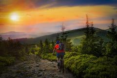 Equitação do motociclista da montanha no por do sol na bicicleta nas montanhas do verão dianteiras Foto de Stock Royalty Free