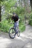 Equitação do motociclista na fuga da floresta do verão Fotografia de Stock Royalty Free