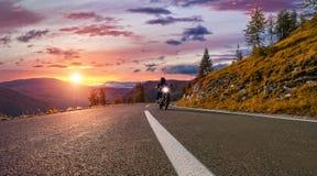 Equitação do motorista de motocicleta na estrada alpina Fotografia exterior, fotografia de stock