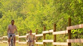 A equitação do pai e da filha bicycles no parque do verão filme
