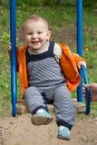 Equitação do rapaz pequeno em um balanço Fotos de Stock Royalty Free