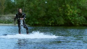 Equitação do Wakeboarder na água tranquilo Vida masculina do extremo do cavaleiro video estoque