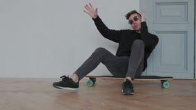 Equitação elegante à moda do homem no longboard ou no skate ao sentar-se O indivíduo move-se, canta-se, e dança Emocional e vídeos de arquivo
