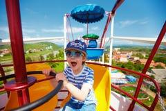 A equitação entusiasmado da criança em ferris roda dentro o parque de diversões imagem de stock