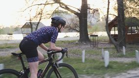 Equitação fêmea apta focalizada do motociclista fora da sela Siga a ideia lateral do treinamento da menina em uma bicicleta Movim filme
