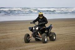 Equitação fêmea de ATV na praia Imagem de Stock