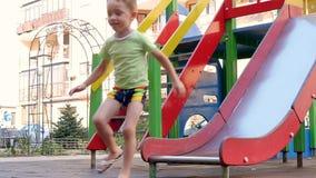 Equitação feliz da criança com uma corrediça das crianças vídeos de arquivo