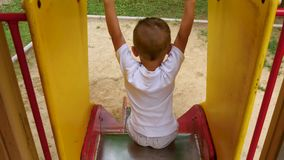 Equitação feliz da criança com uma corrediça das crianças Vista de acima Brincadeiras no campo de jogos video estoque