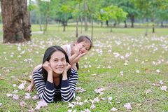 Equitação feliz da menina na parte traseira sua mamã que encontra-se no campo verde com inteiramente a flor do rosa da queda no j fotografia de stock