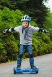 Equitação feliz do menino no hoverboard ou gyroscooter exterior foto de stock