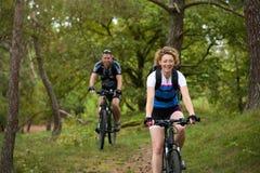 A equitação feliz dos pares bicycles fora imagens de stock royalty free