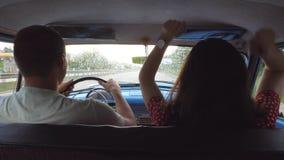 Equitação feliz nova dos pares no carro e na dança do vintage Homem irreconhecível e mulher que sentam-se no assento dianteiro de video estoque