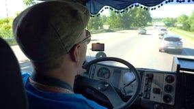 Equitação irreconhecível do motorista de caminhão na estrada do condado no dia ensolarado Homem no tampão e nos óculos de sol que filme