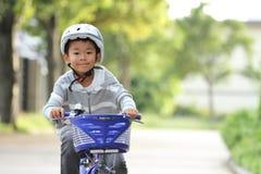 Equitação japonesa do menino na bicicleta Fotos de Stock