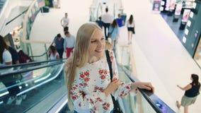 Equitação loura nova da mulher na escada rolante Mulher surpreendida no shopping Jovem senhora no equipamento elegante que monta  filme