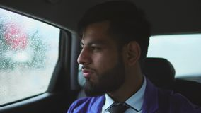 Equitação muçulmana nova do homem de negócios no carro no assento do ` s do passageiro vídeos de arquivo