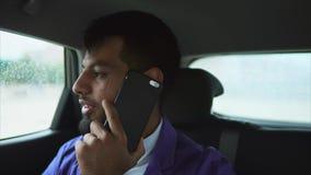Equitação muçulmana nova do homem em um carro no banco traseiro e fala em um smartphone filme