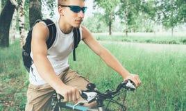 Equitação nova do ciclista na bicicleta no parque do verão imagem de stock