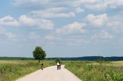 A equitação nova do grupo bicycles pela estrada suja no campo, ciclistas em uma maneira entre árvores, ciclistas novos do grupo q Imagem de Stock