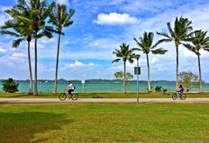A equitação nova dos pares bicycles em um parque da praia Foto de Stock