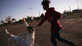 A equitação nova feliz dos pares no trole no estacionamento vazio da alameda, amigo do moderno tem o bom tempo após a compra, par video estoque