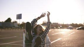 A equitação nova feliz dos pares no trole no estacionamento vazio da alameda, bom amigo tem o bom tempo após a compra, par no amo video estoque