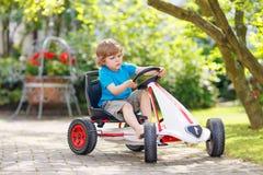 Equitação pré-escolar pequena do menino da criança com sua primeira bicicleta verde Imagens de Stock
