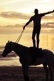 Equitação suprema no por do sol Imagem de Stock