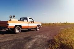 Equitação velha do camionete ao longo de uma estrada de exploração agrícola com um rancho e dos cavalos no fundo no por do sol em Imagens de Stock Royalty Free