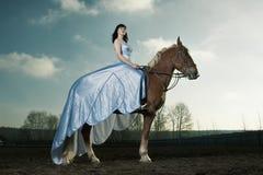 Equitação bonita da mulher em um cavalo marrom Fotografia de Stock Royalty Free