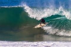 Equitação do surfista sob o bordo oco da onda Fotos de Stock Royalty Free