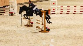 equitation visa banhoppningen, hästen och ryttaren över hopp Arkivbild