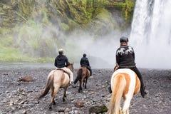 Equitazione alla cascata di Skogafoss, Islanda immagini stock libere da diritti