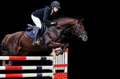 Equitazione: Ragazza nella manifestazione di salto, isolata sul nero Fotografie Stock