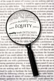 Equity. Magnifying glass over document, highlighting the word equity.  Searching for principles of conduct Royalty Free Stock Image