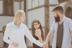 Er ist nichts aber ein Frauenheld Hippie, der zwischen zwei Frauen wählt Bärtiger Mann, der anderes Mädchen betrachtet Verrat und stockbilder
