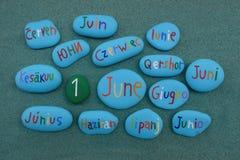 1er juin sur les pierres colorées dans beaucoup de langues au-dessus du sable vert Photographie stock libre de droits