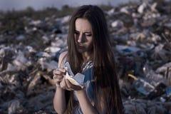Er Mädchen am Dump versucht, die Stücke der defekten Schale zu kleben Stockfoto