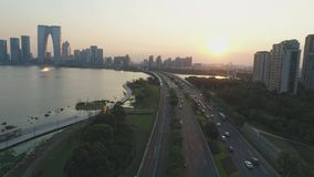 1er octobre 2018 Ville de Suzhou, Chine Vol aérien de bourdon au-dessus de route dans le secteur moderne sur le coucher du soleil banque de vidéos