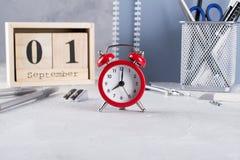 1er septembre Calendrier en bois, groupe de fournitures scolaires, réveil rouge sur une table grise Photos stock