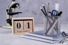 1er septembre Calendrier en bois, groupe de fournitures scolaires sur une table grise Photos libres de droits