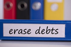 Erase debts on blue business binder Royalty Free Stock Photos