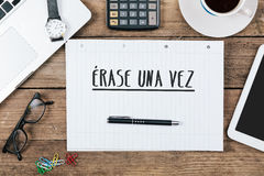 Erase una vez, Spanish text for Once Upon a Time on note pad at. Erase una vez, Spanish text for Once Upon a Time, on note pad at office desk with electronic Stock Photography