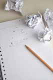 Erase the Words Idea on White Paper. Pencil point to erase words idea on paper with crumpled paper throw around Stock Photos