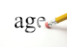 Erase your age. The word age written with a pencil on white paper.  An eraser from a pencil is starting to erase the word age Royalty Free Stock Image